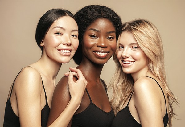 Multi Ethnic Group of three young women with diffrent types of skin  together and looking on camera, smiling